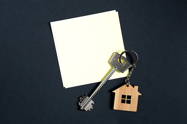 Keychain in the shape of wooden house with key on a black background with a square sheet for notes. building, design, project, moving to new house, mortgage, rent and purchase real estate. copy space