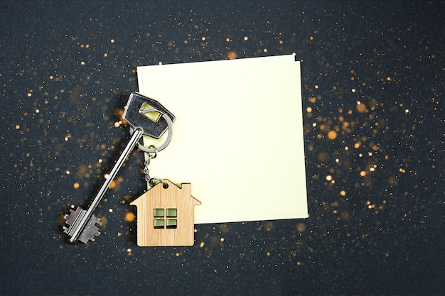 Keychain in the shape of wooden house with key on a black background with a square sheet for notes.