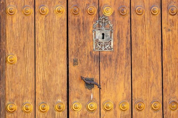 Замочная скважина в старой деревянной двери с панелями; ржавый и выветрившийся