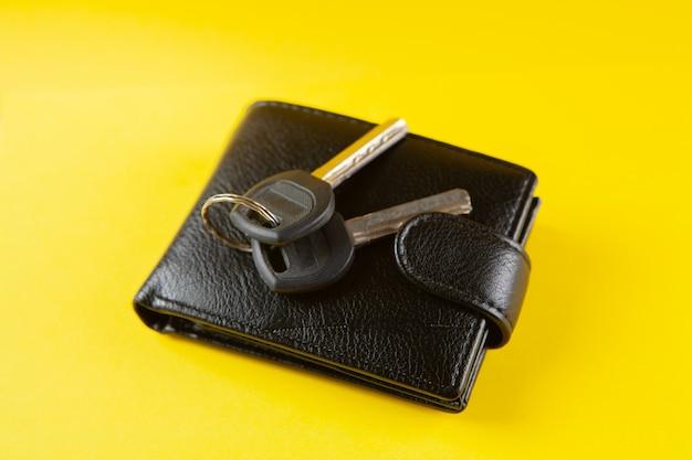 Ключи и черный кошелек на желтой сцене
