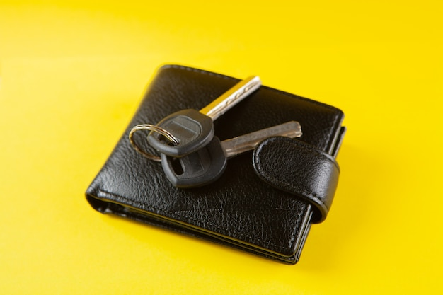 Keys and black wallet on a yellow scene