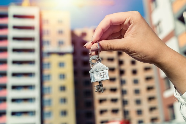 Keys from new home in broker hands on house. sale or rent concept