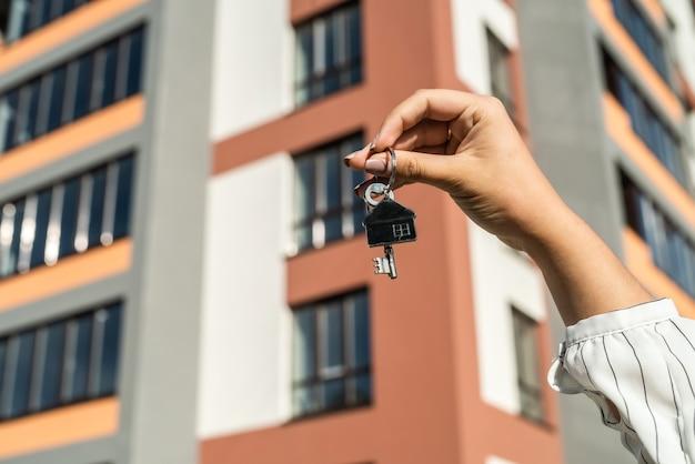 집 배경에 브로커 손에 새 집에서 키. 판매 또는 임대 개념