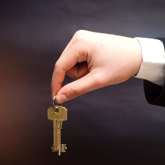 Keys in hands on a black background, concept of selling real estate, buying new apartment