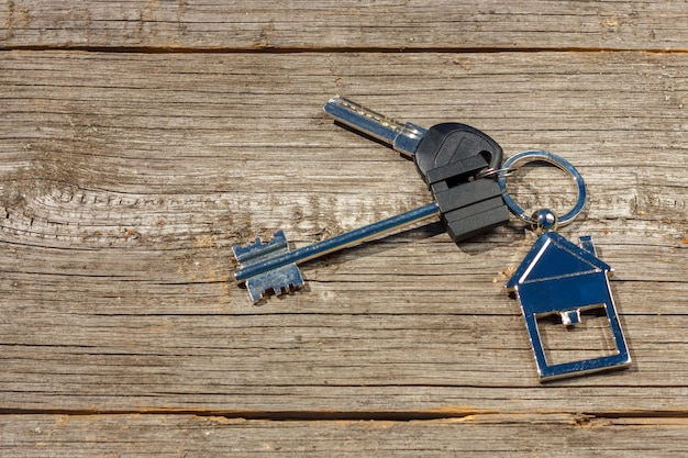 The keys to the house lie on a wooden table