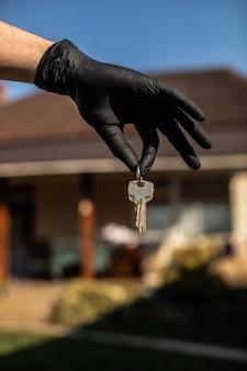 黒い手袋で手にキー。アルコールスプレーを使用して、定期的に家やオフィスの鍵でコロナウイルスや細菌を殺します。 covid-19 ncovまたはコロナウイルス検疫の概念。