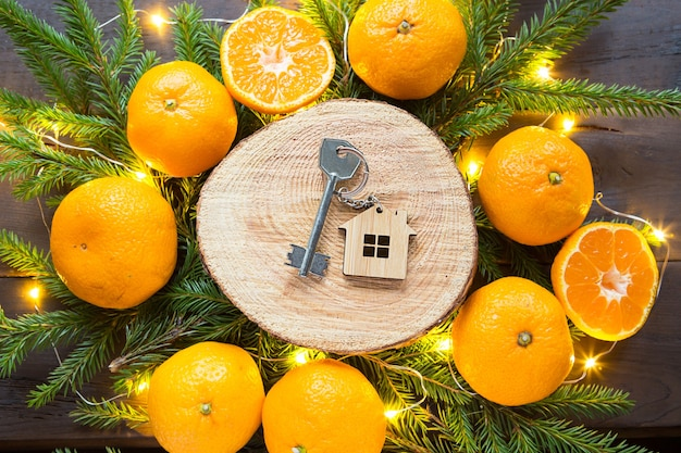 Keys to new house on round cut of tree by tangerines, live fir branches and lights garlands. transfer, shares of the mortgage, the rental of a cottage.