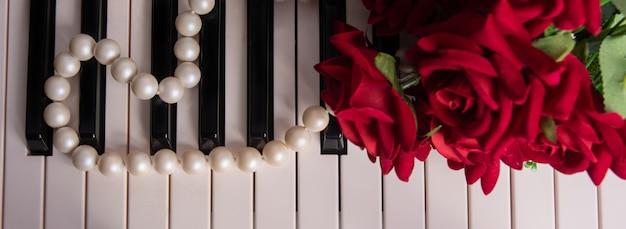 진주 목걸이와 장미 꽃다발이 달린 피아노 키