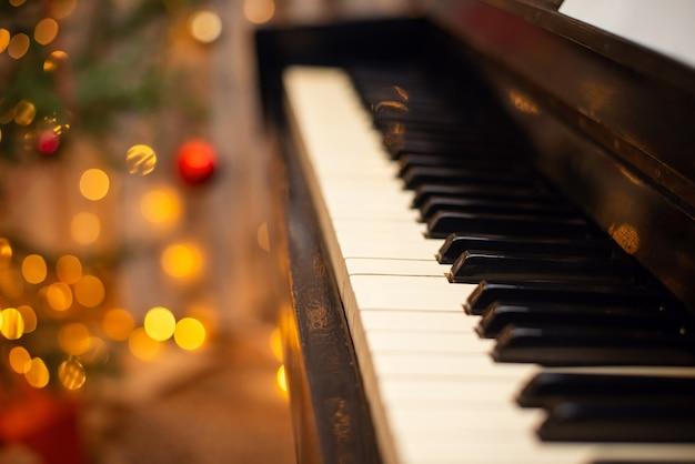 피아노 건반이 닫히고 축제 크리스마스 장식과 배경 조명이 있습니다. 휴일 엔터테인먼트, 음악 반주 개념.