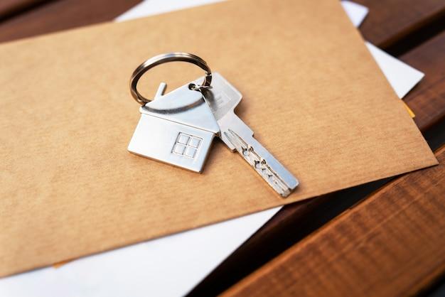 Ключи на столе вместе с документами о недвижимости, ключи от собственника от арендатора квартиры или дома, купли-продажи недвижимости.