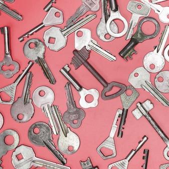 Ключи на розовом фоне. ключи от дверных замков и сейфы для сохранности имущества и охраны дома.