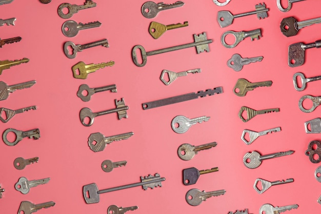 Keys set on pink background. door lock keys and safes for property security and house protection. different antique and new types of keys.