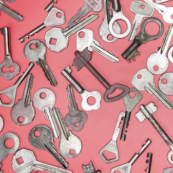 Keys set on pink background. door lock keys and safes for property security and house protection.