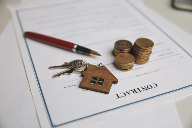 Keys on a signed contract of house sale and pen.