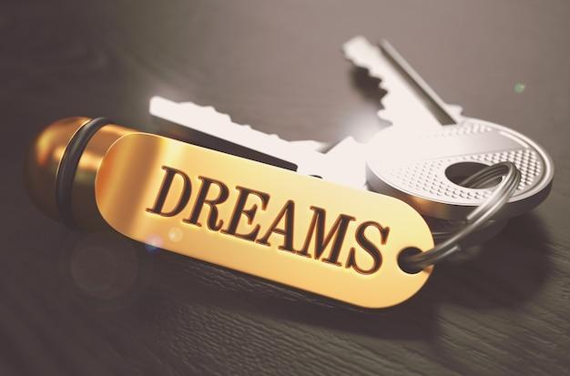 Ключи к мечтам - концепция на золотой брелок на черном деревянном фоне.