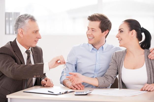 Ключи от вашего нового дома! молодая пара вместе сидит за столом, пока старший мужчина в строгой одежде дает им ключ и улыбается