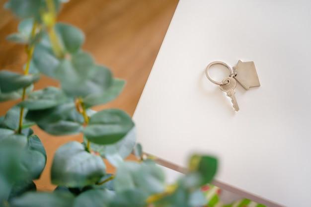 집 형태의 열쇠고리가 있는 열쇠가 새 집의 흰색 탁자에 놓여 있다