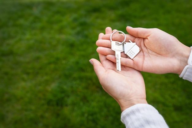 Ключи с брелком в виде металлического домика от нового дома или квартиры в руках девушки на фоне зеленой травы.