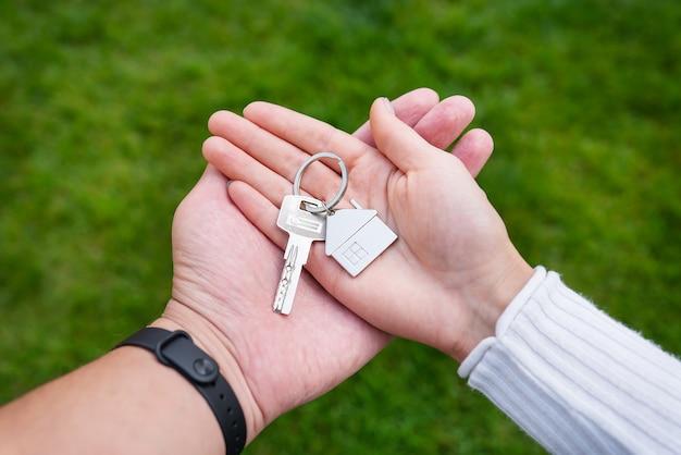 Ключи на брелке в виде металлического домика от нового дома или квартиры в руках молодой семьи. счастье от покупки дома.