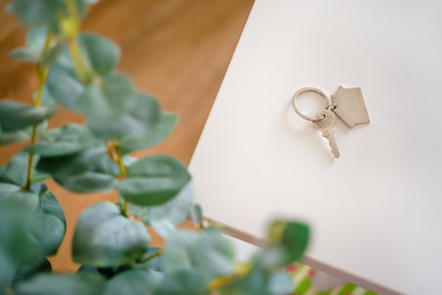 Keys with a keychain in the form of a house are lying on a white table in a new house