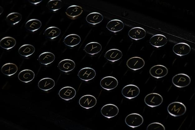 古代の黒いタイプライターの文字が付いているキー