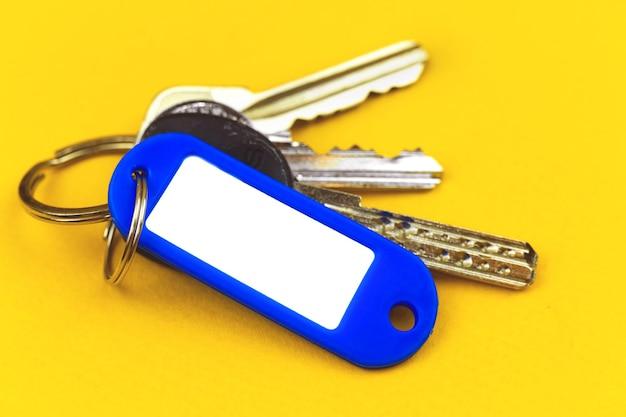Ключи с макетом пластикового значка с копией пространства, концепция покупки новой недвижимости, фото на желтом фоне