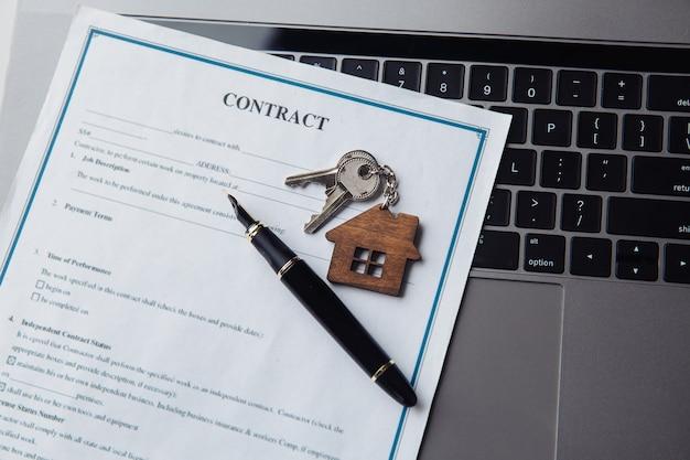 Ключи с деревянным домиком и контрактом на ноутбуке. понятие аренды, поиска, покупки недвижимости