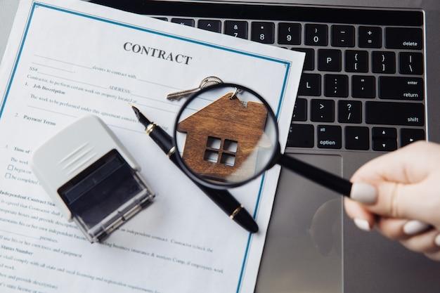 Ключи с деревянным домиком, увеличительным стеклом и контрактом на ноутбуке. понятие аренды, поиска или ипотеки.