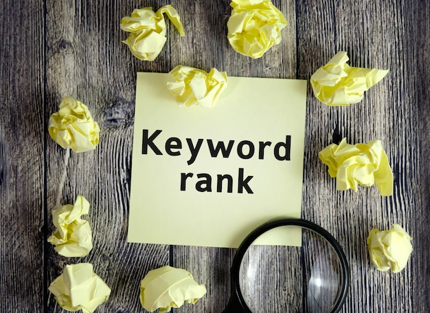 Keyword rank - text on yellow note sheets on a dark wooden background with crumpled sheets and a magnifying glass