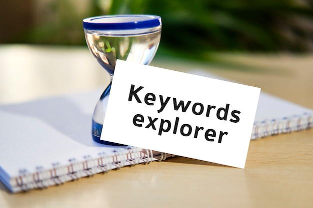 Keywords explorer - business seo concept text on a white notebook and hourglass clock, green leaves of flowers