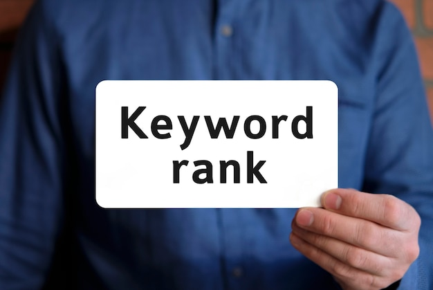 Keywords rank - text on a white sign in the hand of a man in a blue shirt