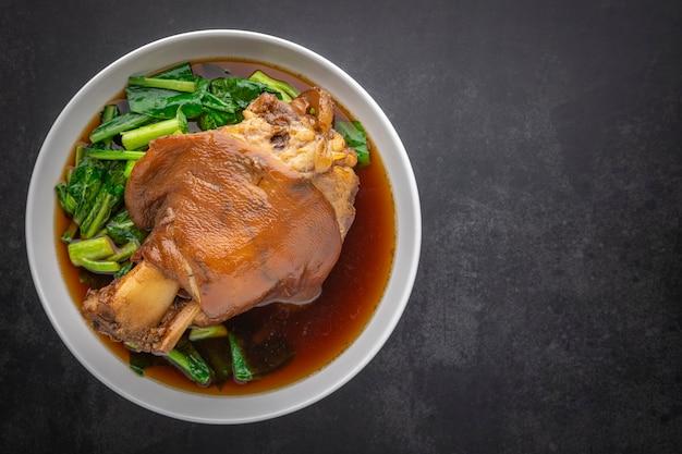 Kha moo pa lo、タイ料理、テキスト用のコピースペース付きの暗い色調のテクスチャ背景に甘い茶色のソースで茶色の中国風豚足を煮込んだ、上面図のショット