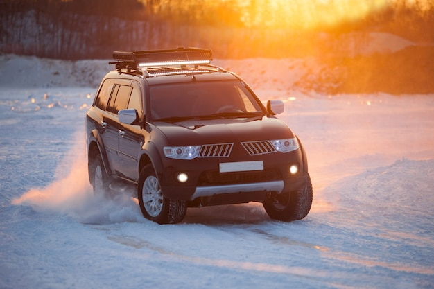 Khabarovsk, russia - january 28, 2017: mitsubishi pajero sport moving on ice of a frosn river at sunset