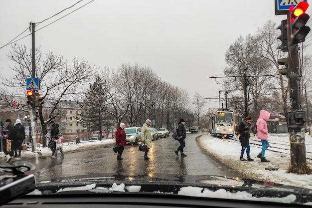 ハバロフスク、ロシア-2020年3月19日:横断歩道の人々は雨の春の朝