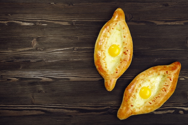 Khachapuri in adjarian. open pie with mozzarella and egg.  caucasian kitchen. bakery products.