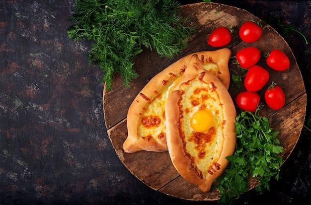 Khachapuri in adjarian. open pie with mozzarella and egg. georgian cuisine.