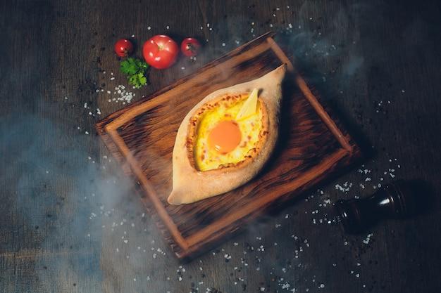 Хачапури крупным планом с яйцом, грузинской кухни. уличная забегаловка.