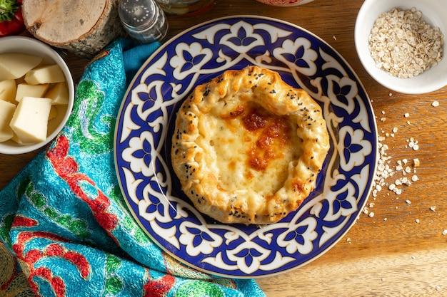 ハチャプリ。伝統的なウズベキスタンのパターンのプレートに生地、スルグニチーズ、卵の温かいオリエンタル料理