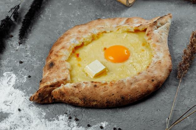 Хачапури по-аджарски. открытый пирог с моцареллой и яйцом. грузинская кухня. Premium Фотографии