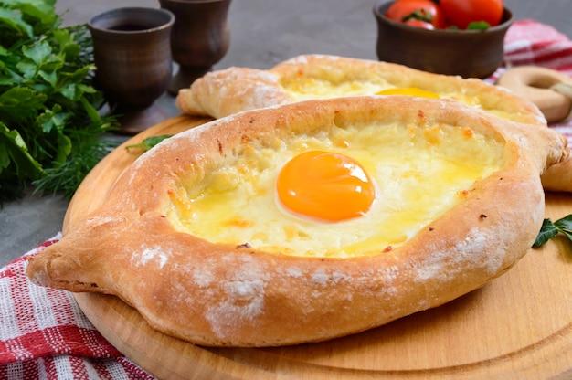 Хачапури по-аджарски. традиционная грузинская и армянская кухня. открытый пирог с сыром сулугуни и яичным желтком в виде лодки на деревянной доске. вид сверху