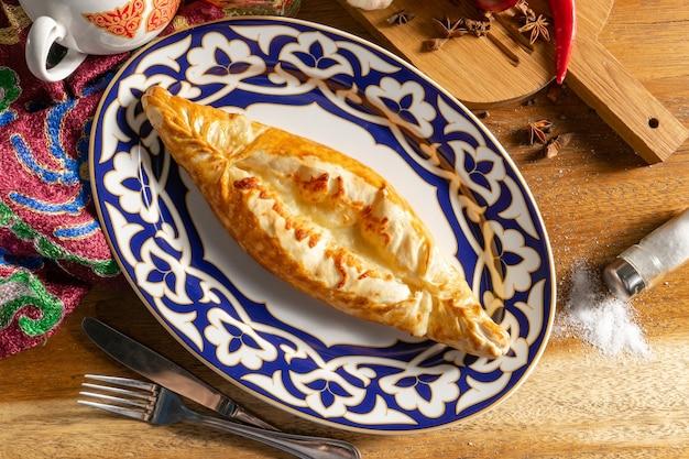 ブハラのハチャプリ。伝統的なウズベキスタンのパターンのプレートに生地、スルグニチーズ、卵の温かいオリエンタル料理