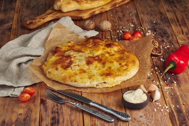 Хачапури по-мегрельски, сырный пирог, грузинский блюдо на деревянном столе