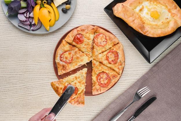 치즈와 토마토, 계란, 야채 조각, 흰색 나무 테이블에 바질과 함께 khachapuri. 피복재. 위에서 봅니다.