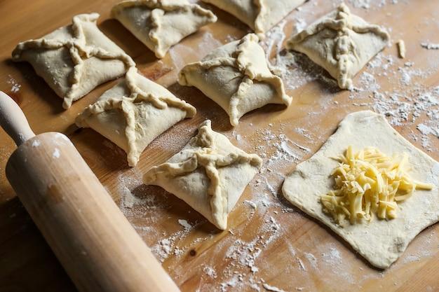 Хачапури с сыром внутри на деревянном фоне мука для рулета из теста с сыром приготовление хачапури мука из теста и скалка на столе слоеное тесто