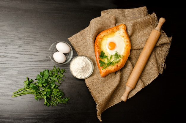 Khachapuri with eggs on sackcloth, flour, eggs and parsley on black table, space for text