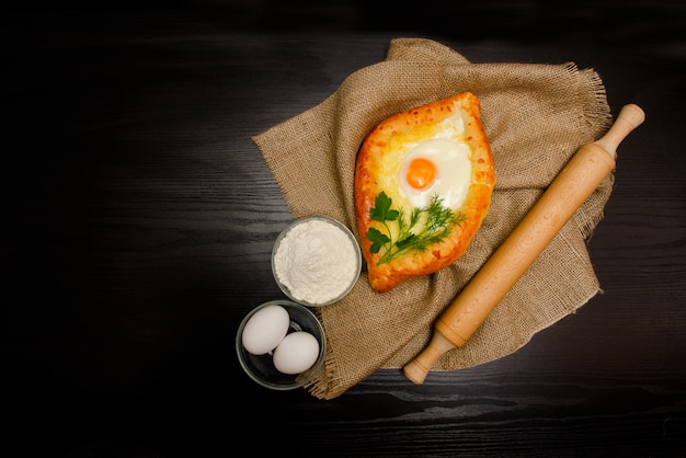 Khachapuri with eggs on sackcloth, flour, eggs and rolling pin on black table, copyspace