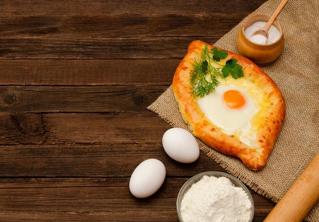 Khachapuri with eggs on sackcloth, salt, flour and eggs. georgian cuisine