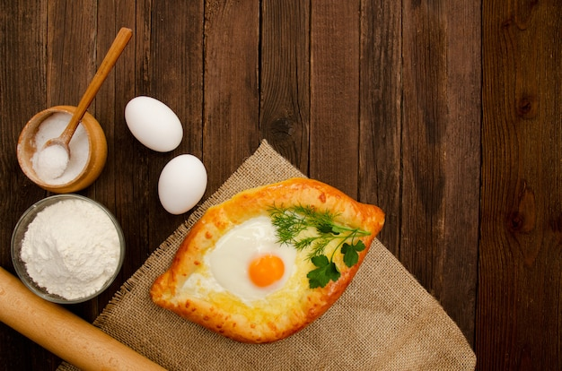 Khachapuri with eggs on sackcloth, salt, flour, eggs and parsley on the wooden table, copyspace