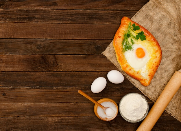 Khachapuri with eggs on sackcloth, salt, flour, eggs and parsley on the wooden table