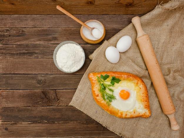 Khachapuri with eggs on sackcloth, salt, flour and eggs. wooden table, copy space